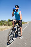 Handsome cyclist taking a break on his bike drinking water