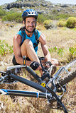 Fit cyclist tying his shoelace on mountain trail smiling at camera