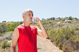 Fit man drinking water on mountain trail