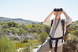 Hiker looking through binoculars on country trail