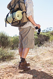 Hiker holding his binoculars on country trail