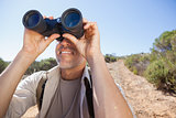 Hiker looking through his binoculars on country trail