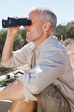 Hiker taking a break on country trail looking through binoculars