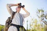 Hiker standing on country trail looking through binoculars