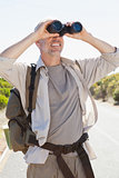 Hiker standing on road looking through binoculars