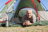 Happy camper smiling at camera lying in his tent