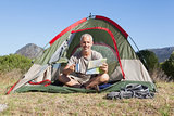 Happy camper looking at map sitting in his tent