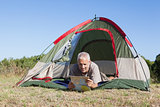 Happy camper looking at map lying in his tent