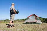 Happy camper walking towards his tent holding sleeping bag