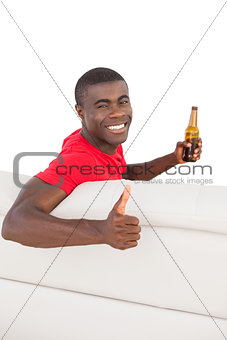 Football fan in red jersey sitting on couch holding beer showing thumbs up