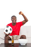 Football fan in red jersey sitting on couch cheering