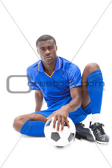 Football player sitting on the ground holding ball