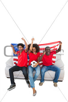 American football fans in red cheering on the sofa