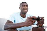 Smiling man sitting on couch playing video games