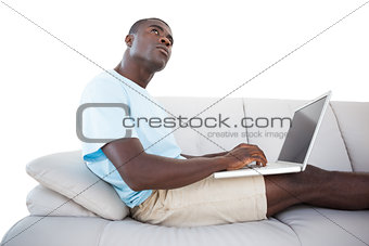Thoughtful man sitting on couch using laptop