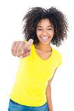 Pretty girl in yellow tshirt and denim hot pants smiling at camera