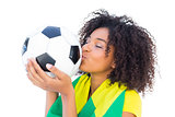 Pretty football fan with brazilian flag kissing ball