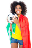 Pretty football fan with portugal flag holding ball