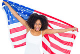 Pretty cheering girl in white top holding american flag