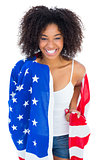 Pretty girl wrapped in american flag smiling at camera