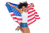 Pretty girl wrapped in american flag jumping and smiling at camera