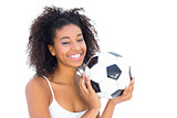 Pretty girl holding football and smiling at camera