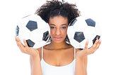 Pretty girl holding footballs and looking at camera