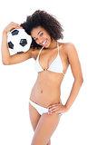 Smiling fit girl in white bikini holding football