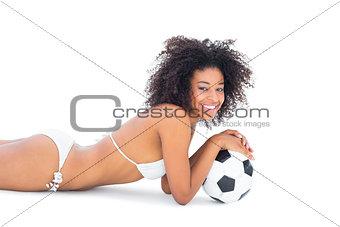 Fit girl in white bikini holding football lying on floor