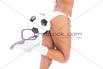 Fit girl in white bikini holding football at her foot