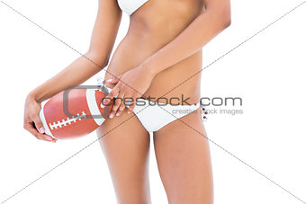 Fit girl in white bikini holding american football