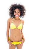 Slim girl in yellow bikini smiling at camera