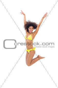 Fit girl in yellow bikini jumping and smiling at camera