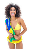 Fit girl in yellow bikini holding brazil flag smiling at camera