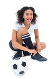 Pretty football player in white tying her shoelace