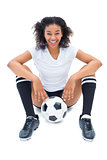 Pretty football player in white sitting on floor with ball