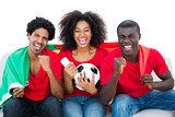 Cheering football fans in red sitting on couch with portugal flag
