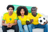 Excited football fans in yellow sitting on couch with brazil flag