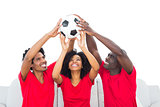 Happy football fans in red holding up ball
