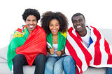 Happy football fans wrapped in flags smiling at camera