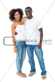 Casual couple in jeans and white tops smiling at camera