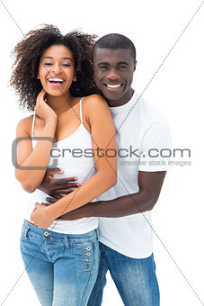 Casual couple embracing and smiling at camera