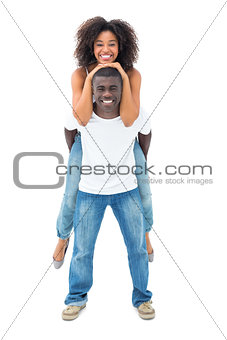 Casual man giving his smiling girlfriend a piggy back