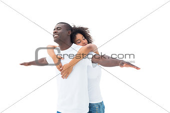 Casual couple standing with arms outstretched