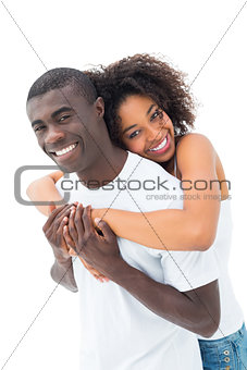 Casual couple hugging and smiling at camera