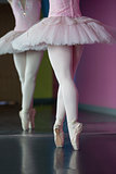 Graceful ballerina standing en pointe in front of mirror