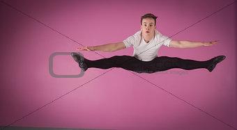 Focused male ballet dancer leaping doing the splits
