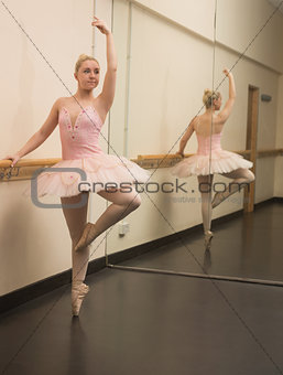 Beautiful ballerina standing en pointe with the barre