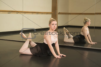 Beautiful ballerina posing in front of mirror