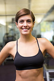 Fit brunette in black sports bra smiling at camera